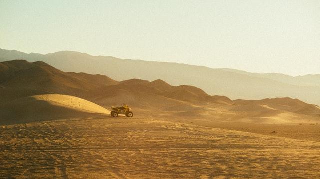 Štvorkolka zaparkovaná na piesku na púšti.jpg