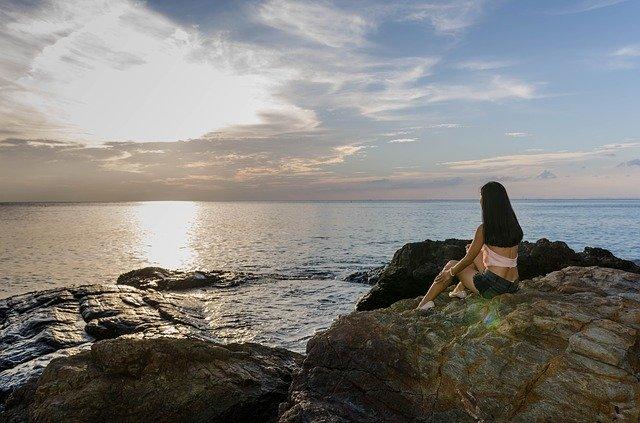 Žena sedí na skalách pri mori v zátoke za súmraku.jpg
