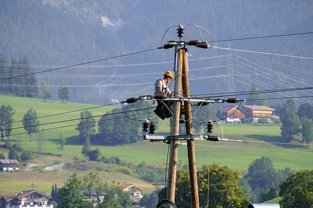 Muž sedí na kábloch vysokého napätia a niečo montuje.jpg