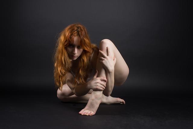 Žena s ryšavými vlasmi v bielom tielku sedí na zemi.jpg
