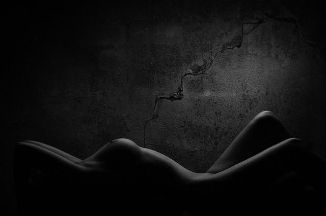 Nahá žena pred sivou betónovou stenou s prasklinou.jpg