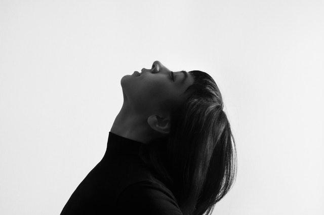 Žena v čiernom roláku so zaklonenou hlavou