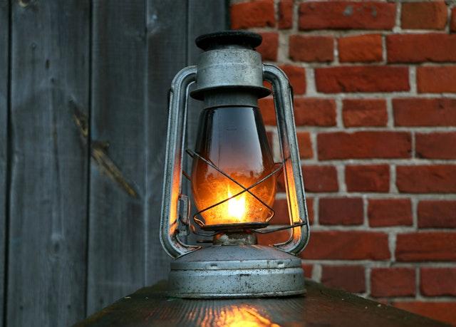 Lampáš so zapálenou sviečkou pri tehlovej stene a drevených dverách