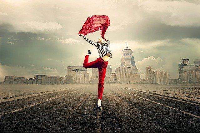 Žena tancuje uprostred ulice s červenou šatkou v rukách